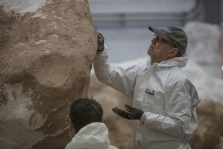 William Tucker at work on the surface of the sculpture