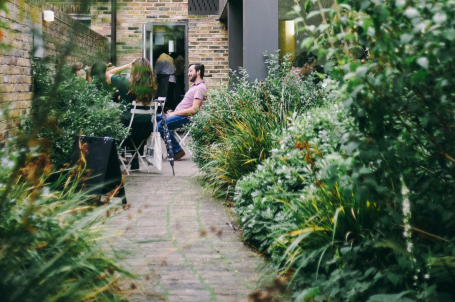 Outdoor cafe seating with planting in the foreground