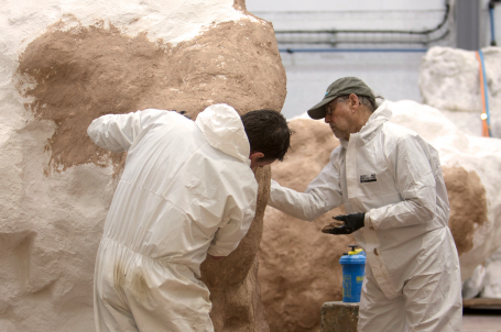 Two men working on the surface of a large sculpture