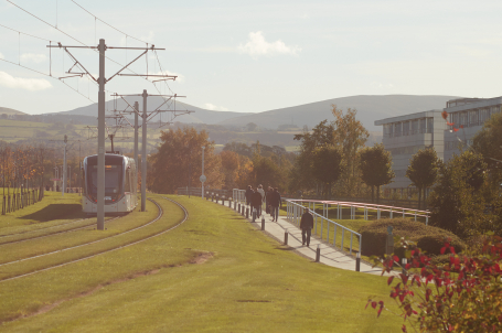 Scene with tram, pedestrians and green space
